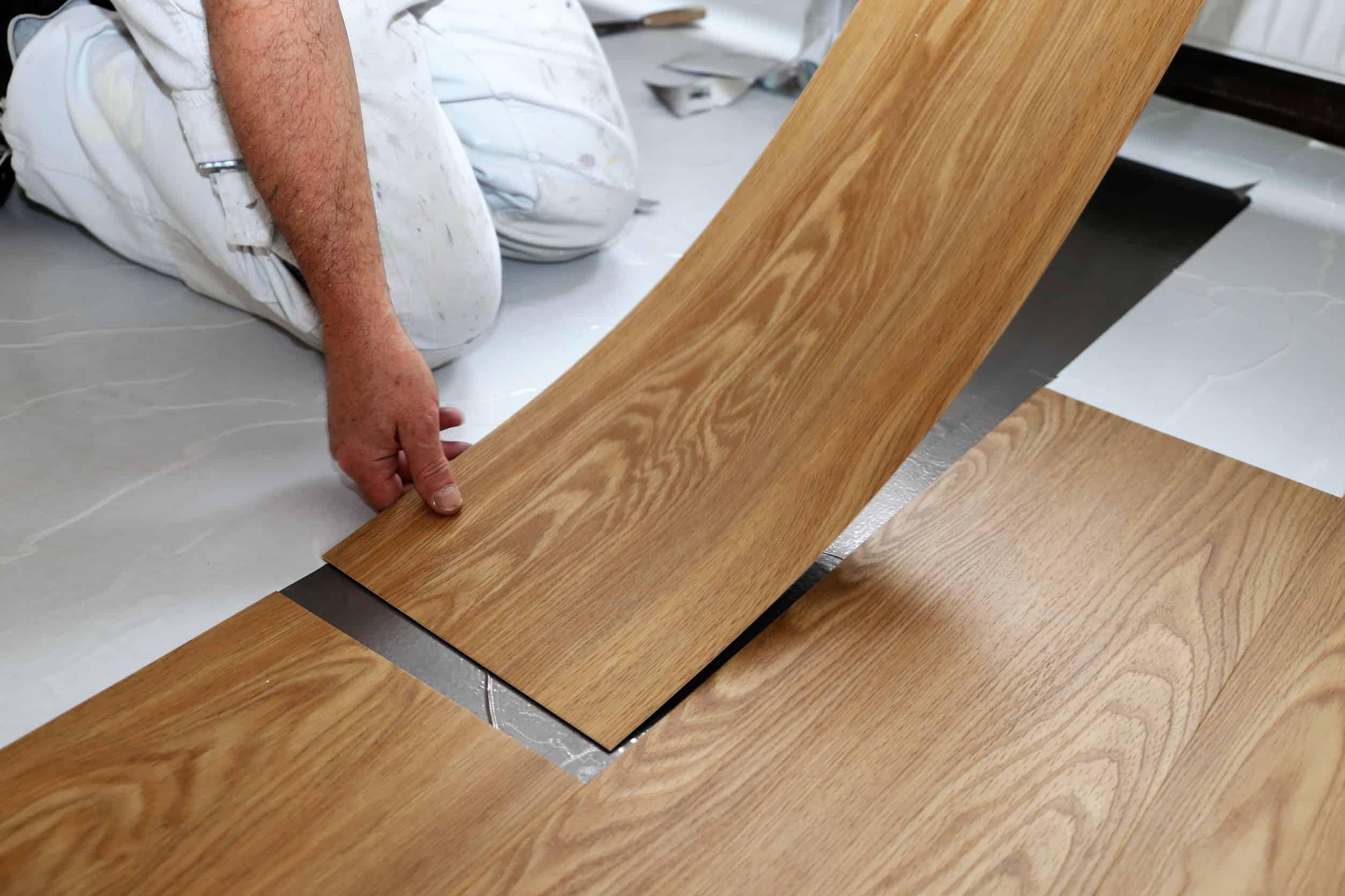 man installing vinyl tiles
